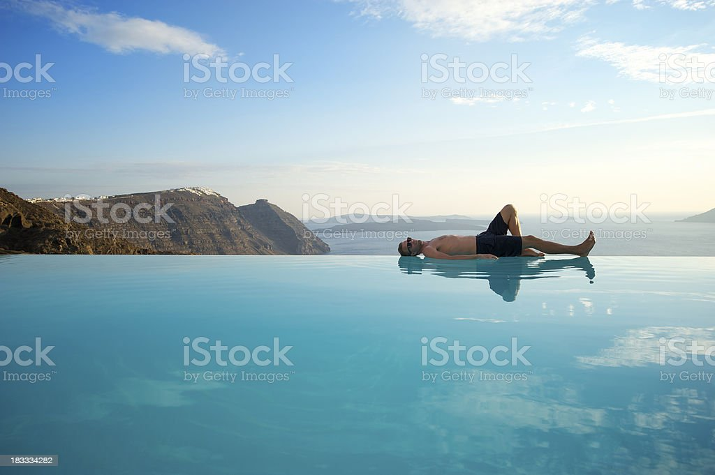 Man on infinity pool edge in Santorini, Greece royalty-free stock photo