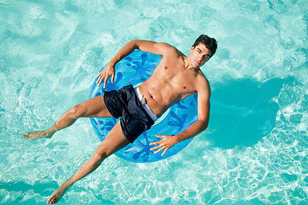 Man on inflatable ring in pool  swimwear stock pictures, royalty-free photos & images