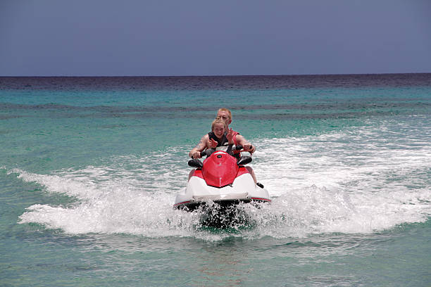 man on jet ski with girl stock photo