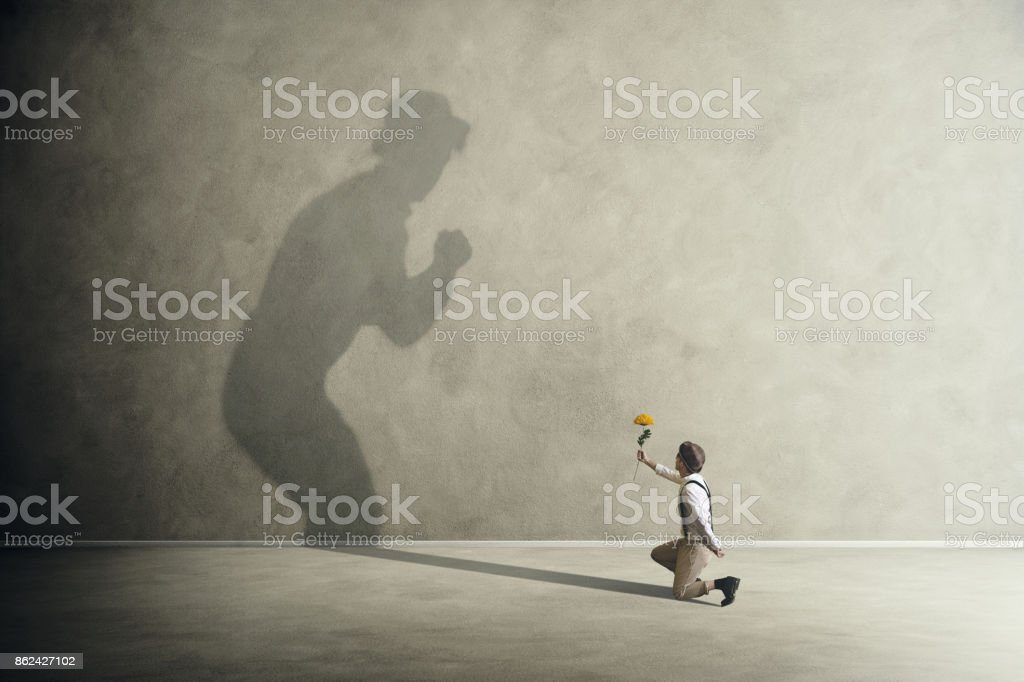 Man on knees with flowers making peace with his shadow stock photo