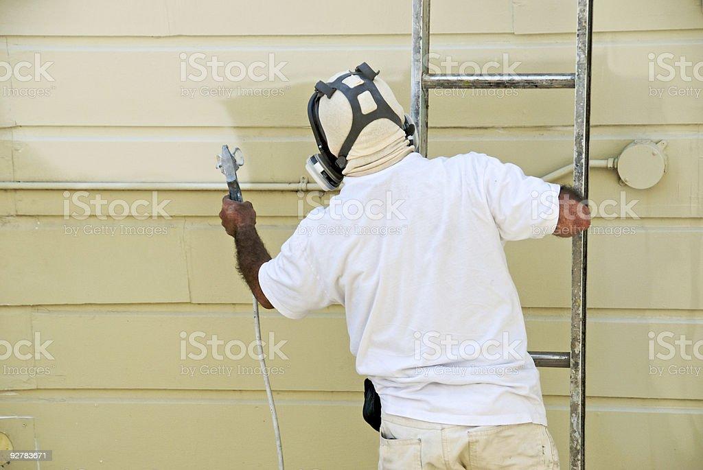 Man on ladder painting with spray gun stock photo