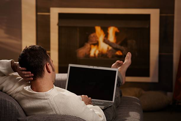 Man on laptop, relaxing with his feet up by the fireplace stock photo