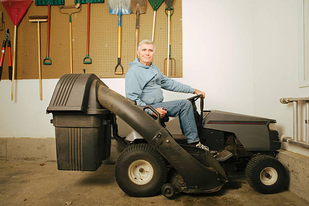 man on lawn mower in garage, portrait - riding lawn mower stock photos and pictures