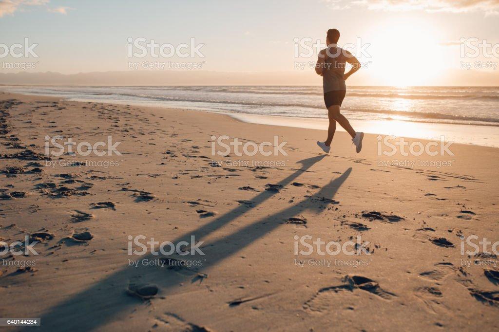 Man on morning run at the beach stock photo