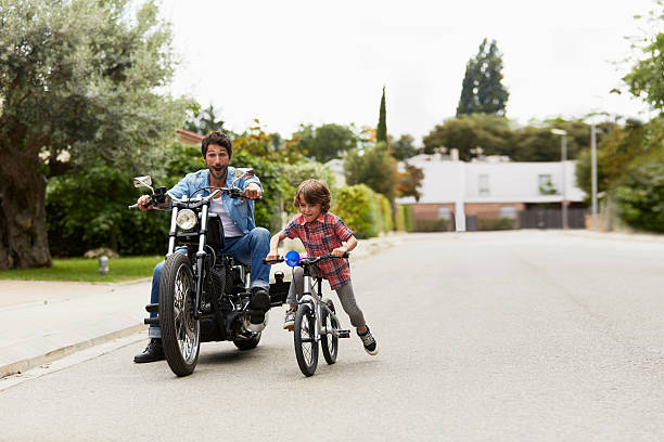 man on motorbike chasing son riding bicycle - motorbike racing stock photos and pictures