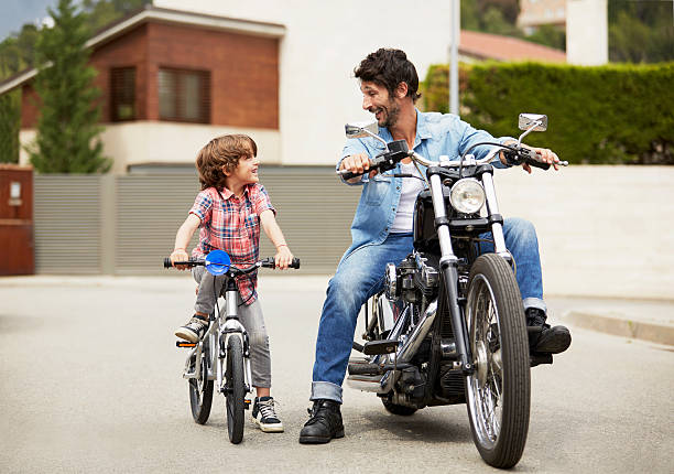 man on motorbike looking at son riding bicycle - take care of your jeans imagens e fotografias de stock