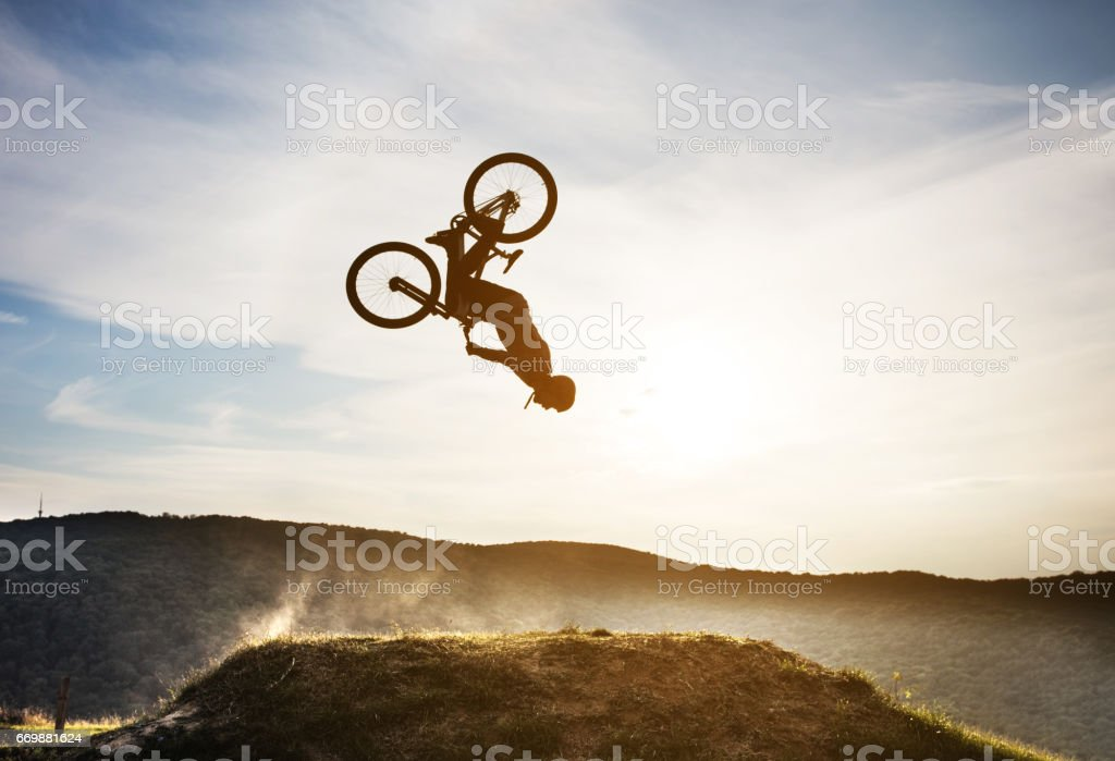 Man on mountain bicycle performing backflip in nature. stock photo
