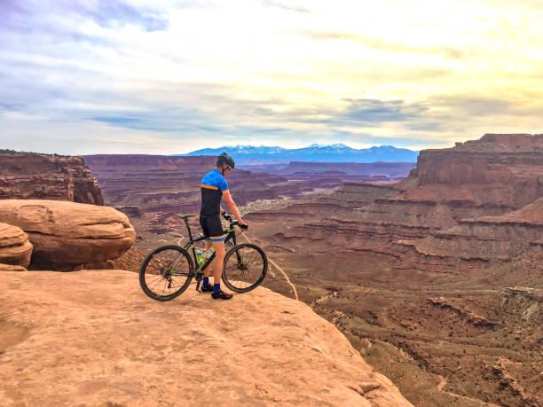 man op de mountainbike op de rand van de klif - moab utah stockfoto's en -beelden