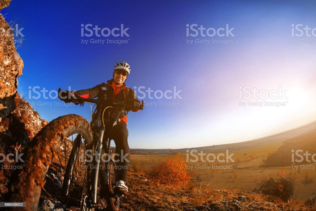 Man on mountain bike on the background of beautiful sunset. Bicycle wheel closeup. royalty-free stock photo