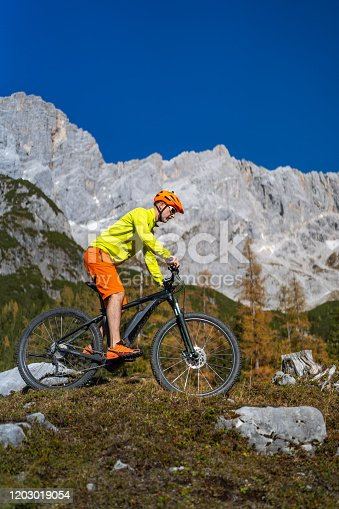 side view vertical outdoor sports shot, man in colorful sport clothes mountainbiking in awesome alpine mountain landscape in austria on sunny day in autumn with clear blue sky, dachstein mountains in background