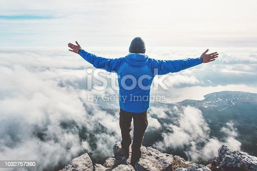 istock Man on mountain cliff enjoying aerial view hands raised over clouds Travel Lifestyle success concept adventure active vacations outdoor freedom emotions 1032757360