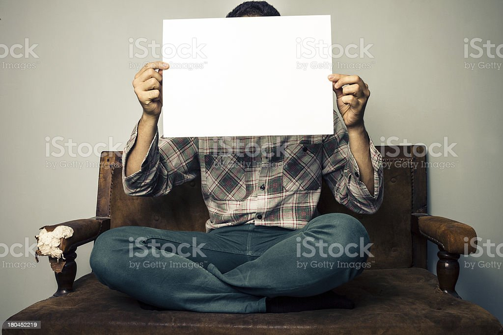 Man on old sofa holding a white sign royalty-free stock photo