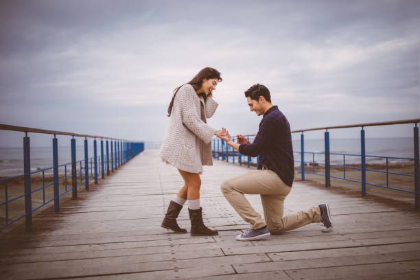 mann auf einem knie schlägt vor, freundin auf einem pier - verlobung stock-fotos und bilder