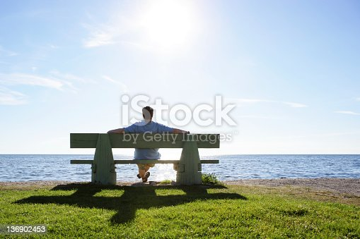 man sitting on park bench overlooking ocean on bright summer day (XL)