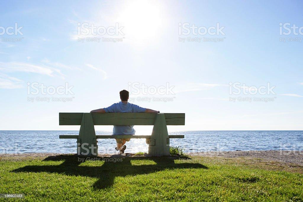 XL man on park bench overlooking ocean stock photo