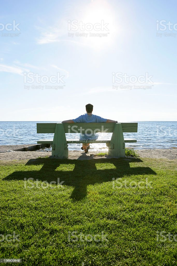 XL man on park bench overlooking ocean royalty-free stock photo