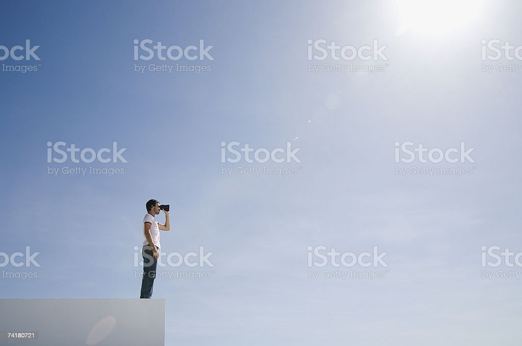 Man on pedestal with binoculars and blue sky outdoors royalty-free stock photo