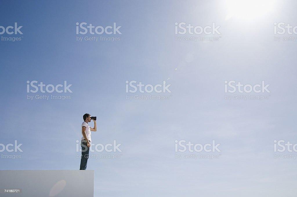 Mann auf Sockel mit Fernglas und blauer Himmel im Freien – Foto