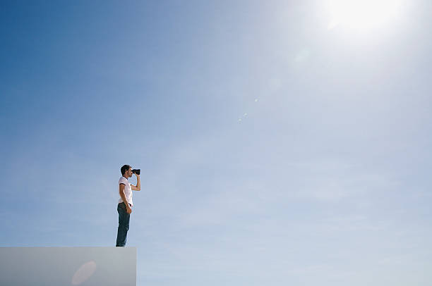 Man on pedestal with binoculars and blue sky outdoors stock photo