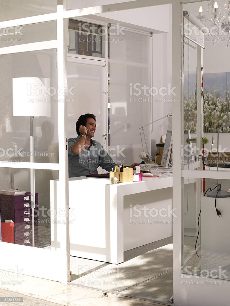 Man on phone at desk royaltyfri bildbanksbilder