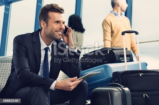 Smiling businessman talking on his mobile phone in an airport lounge.  The man is sitting on the edge of his seat with his phone in his left hand and a digital tablet in his right hand.  He is wearing a black jacket, black pants, a white shirt and a black tie.  There are four suitcases to the left of the image; two of the suitcases are standing upright and two are lying down.  There are other people in the background looking out of the window, waiting for their flight to arrive.
