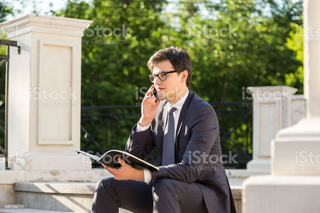 Man on phone holding notepad Стоковые фото Стоковая фотография