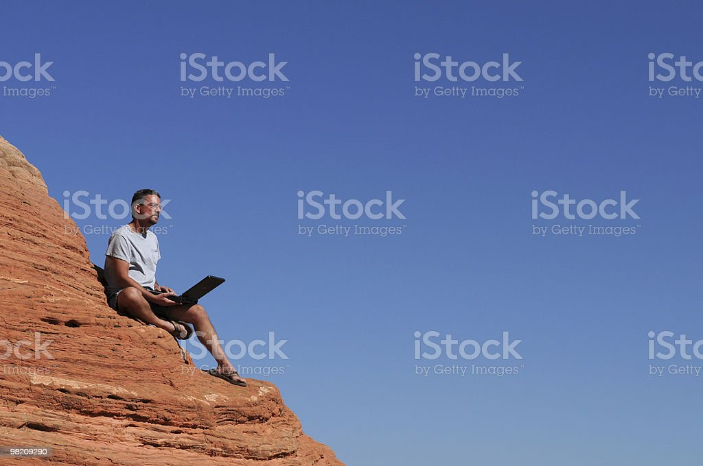 Man on Red Rock with Laptop Computer, Blue Background royalty-free stock photo