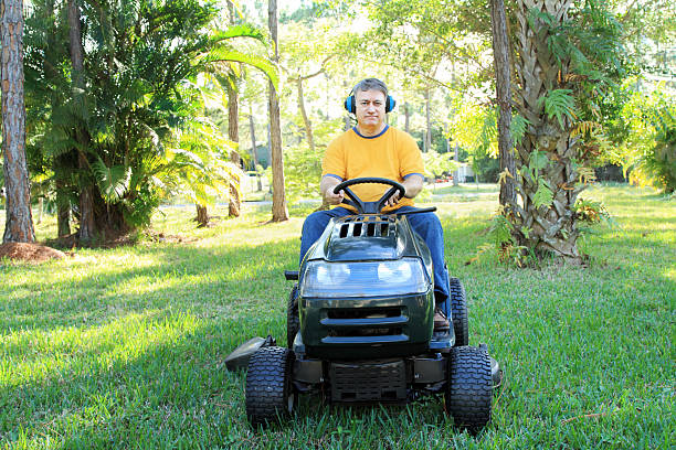 man on riding mower - riding lawn mower stock photos and pictures