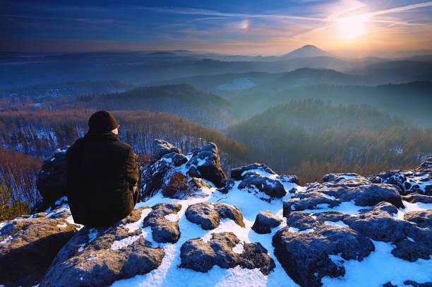Man on rocks and looking at the snow-covered hills. Dark sky stock photo