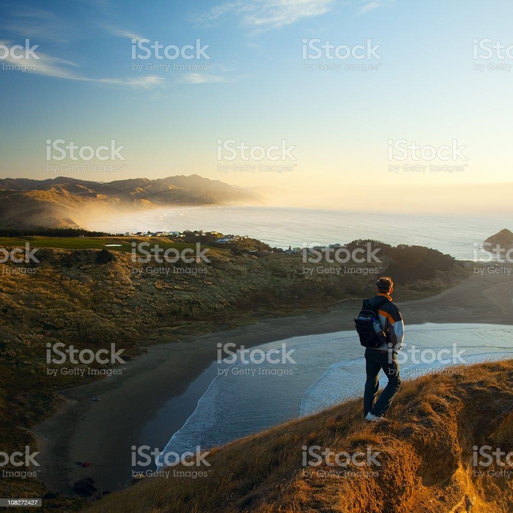Man on rocky coast, morning light stock photo