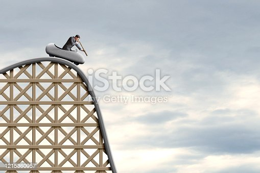 A businessman looks through a spyglass as he sits in a rollercoaster car and surveys what is below him before he takes the ultimate plummet below.