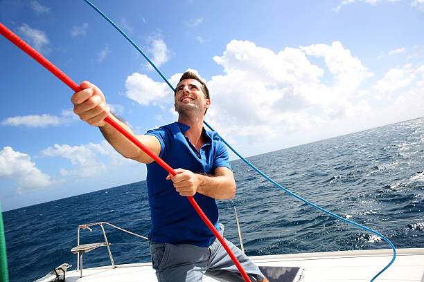 Man on sailboat bordering sail stock photo