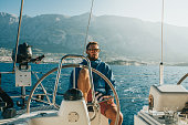 Man in sunglasses sitting on yacht with sea and hills in background,Croatia