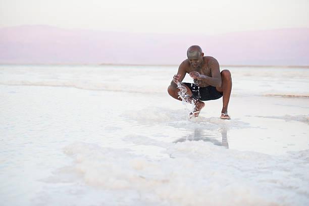 man on salt beach. - flip flops reparieren stock-fotos und bilder