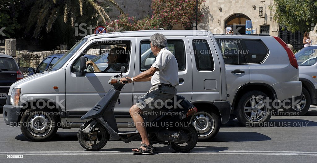Man on scooter with no helmet royalty-free stock photo