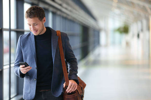 Man on smart phone - young business man in airport stock photo