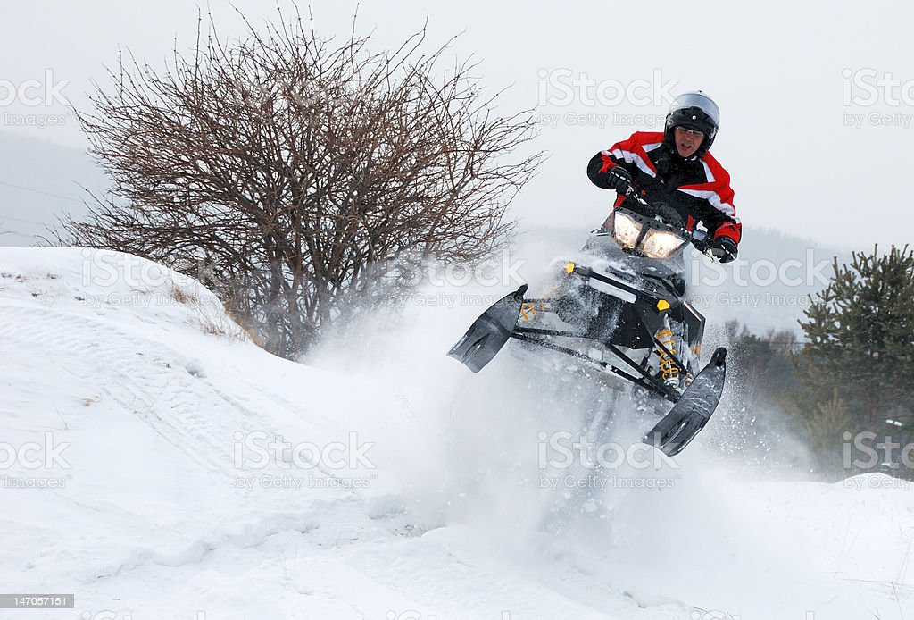 Man on snowmobile jumping stock photo