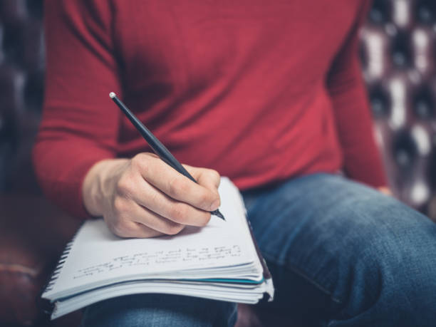 Man on sofa writing in notebook stock photo