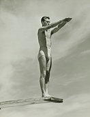Man on springboard ready to jump, (B&W), low angle view