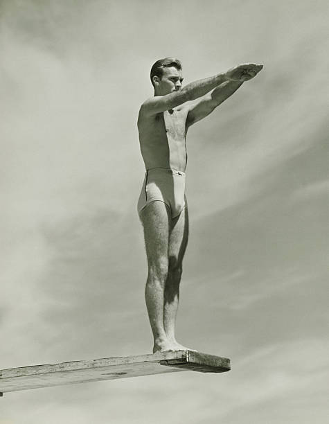 Man on springboard ready to jump, (B&W), low angle view stock photo