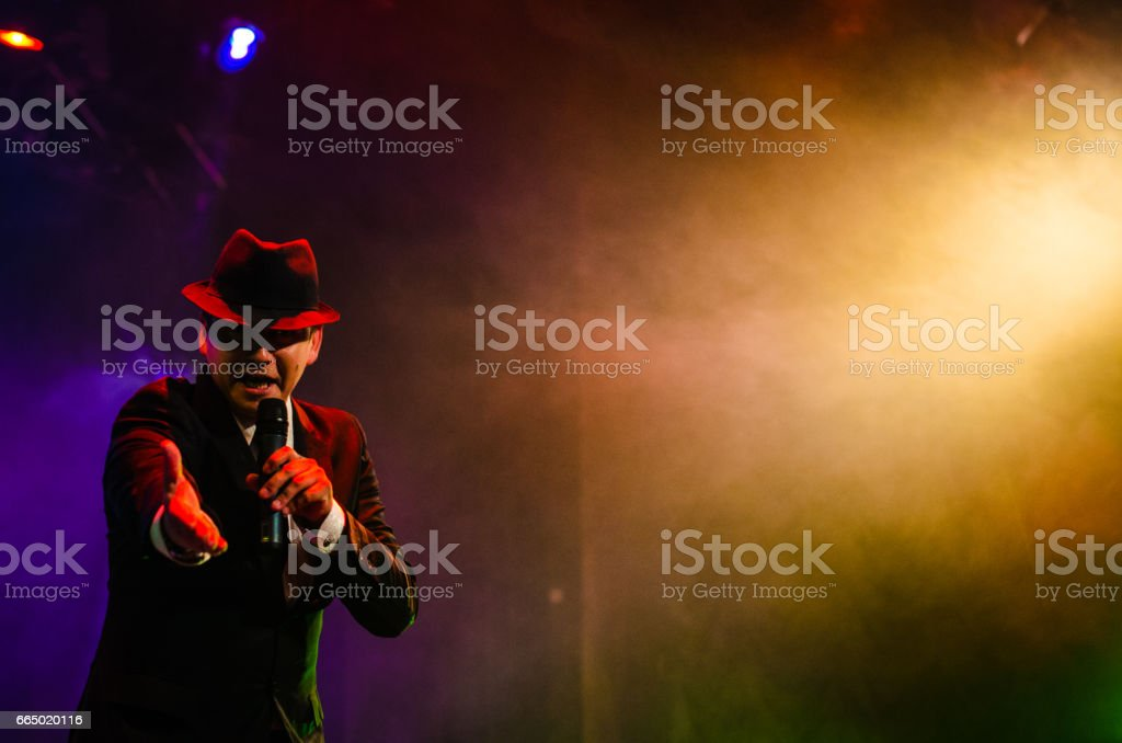 Man on stage talking at the camera stock photo