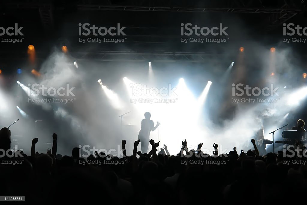 Man on stage with concert crowd below and bright spotlights stock photo
