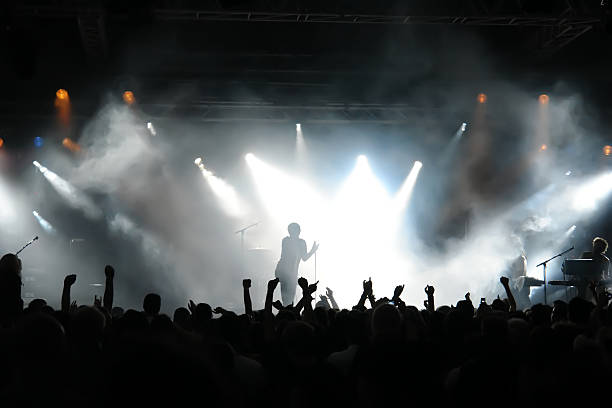 man on stage with concert crowd below and bright spotlights - rock musician stock pictures, royalty-free photos & images