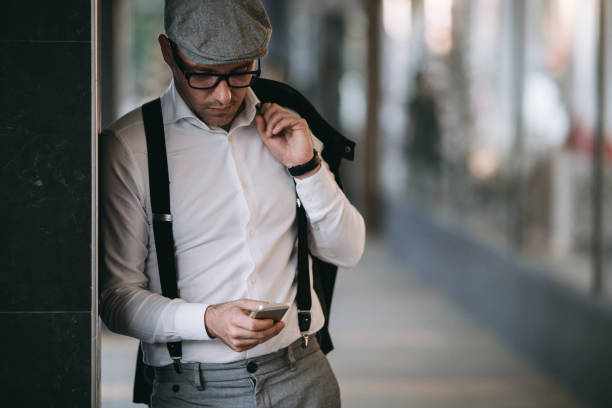 Man on street Fashionable retro dressed man with cap, suspenders and eyeglasses standing on city street and using smart phone. Low angle view. suspenders stock pictures, royalty-free photos & images