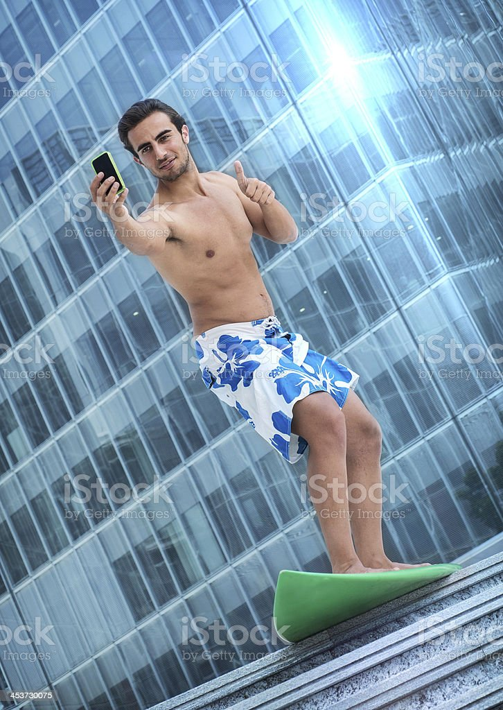 Man on surfboard. Thumbs-up while taking a photo with smartphone royalty-free stock photo