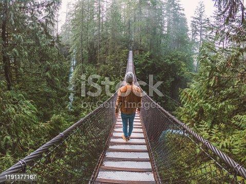 Man walking on suspension bridge crossing canyon in rainforest, river beside, Canada