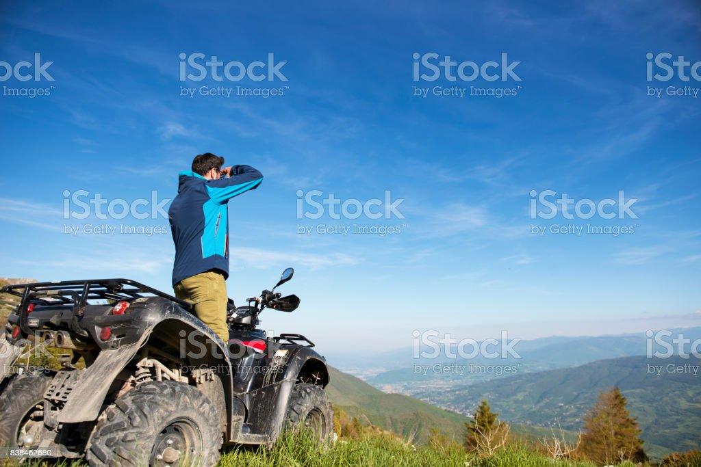 Man on the ATV Quad Bike on the mountains road. stock photo