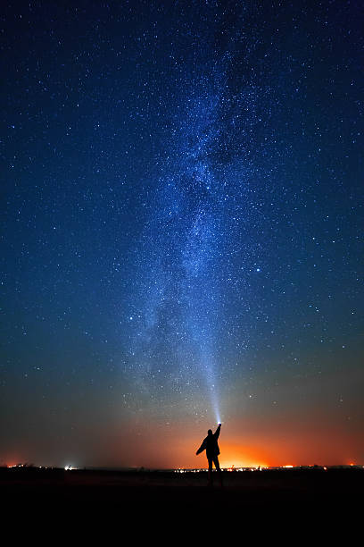 man on the background of bright stars  night sky. The man on the background of bright stars of the night sky. The Milky Way. north star stock pictures, royalty-free photos & images