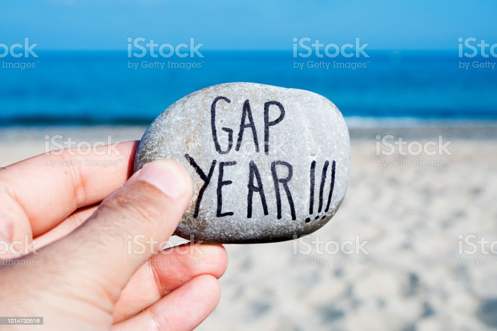man on the beach and text gap year stock photo