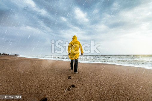 Man on the beach on a rainy day